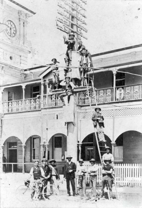 Telegraph pole at the front of the Mackay Post and Telegraph Office in River Street Mackay, c1920