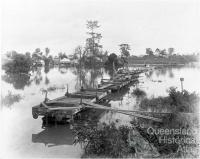 Flat wagons set up as a temporary bridge between Milton and Toowong, c1900