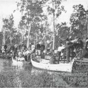 Railway passengers crossing Fitzroy River on flat wagons, c1900